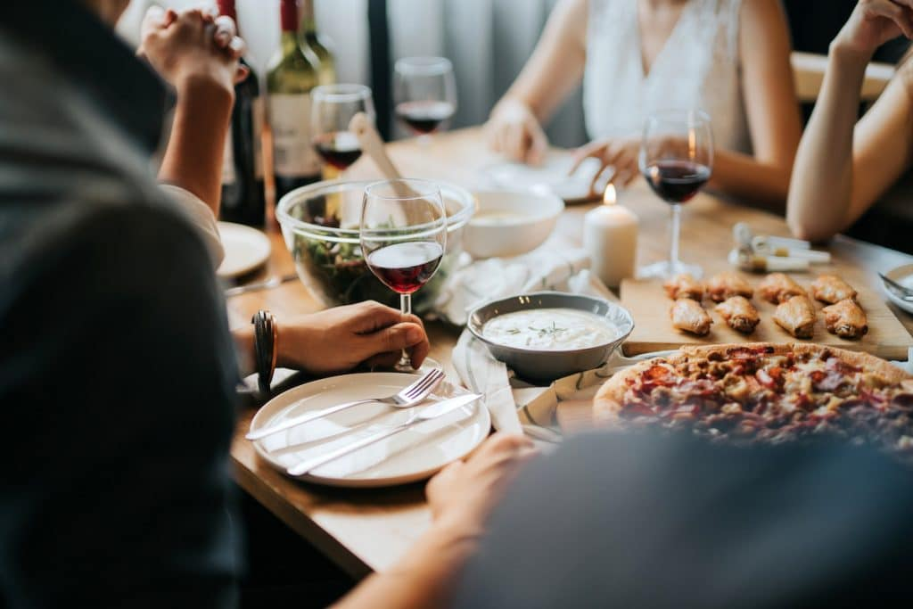 A close up of a group dining at a table with food and wine.