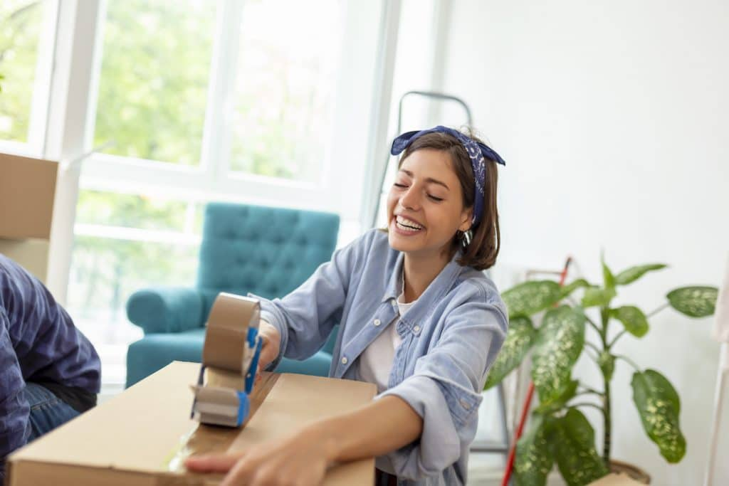 A caucasian woman happily sealing a box with packing tape.