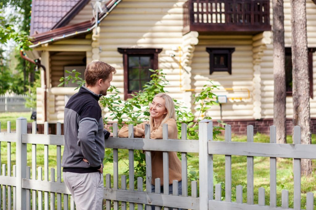 A middle-aged man chatting with a neighbor with a white fence in between them.