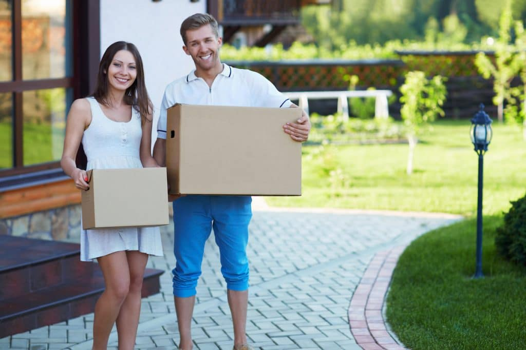 A young couple holding boxes in front of a home.