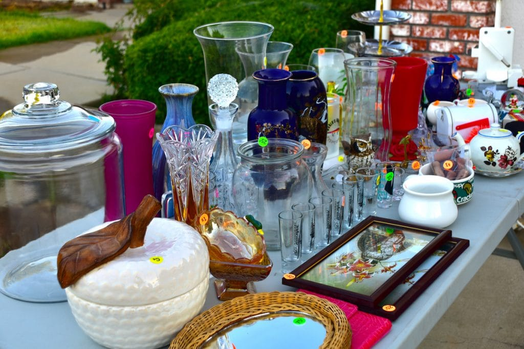 A table filled with glassware and decorative items for sale.