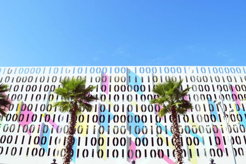 The exterior of Lake Nona Code Wall parking garage with palm trees in front of it.