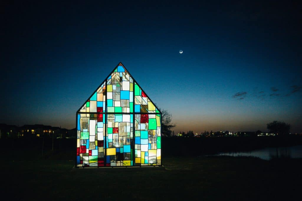 The Glass House art installation at night time.