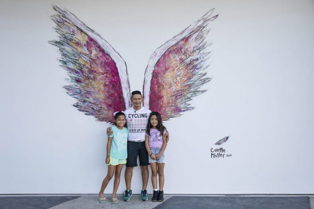 A hispanic dad with children posing by the Lake Nona angel wings painting.