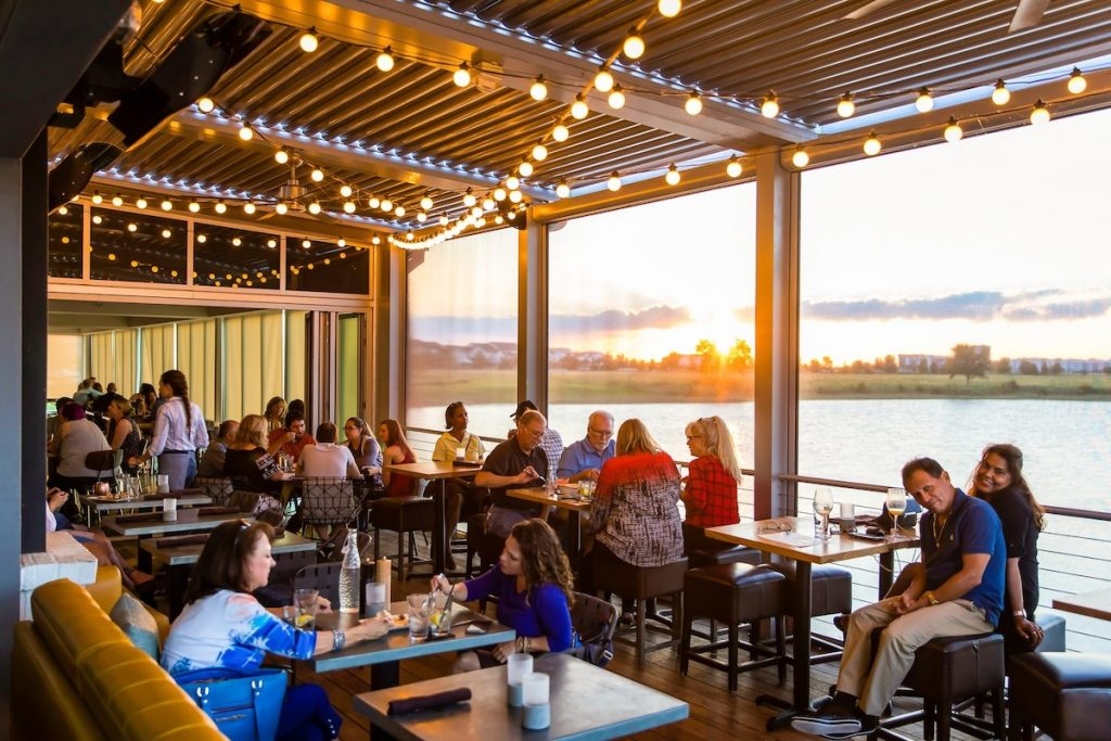 People dining at Canvas restaurant seating area by the lake.