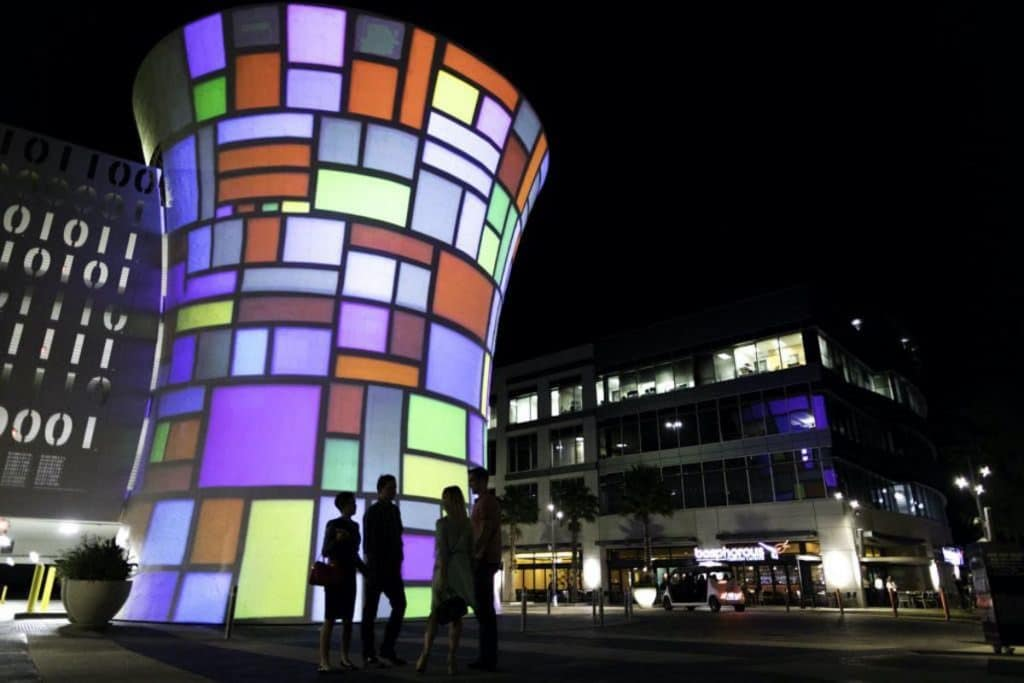 Silhouettes of people standing by the Beacon interactive art installation  at night time.
