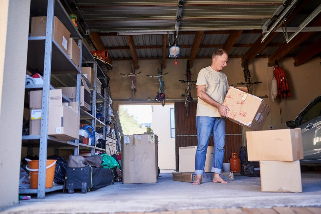 A man stacking boxes in his garage.