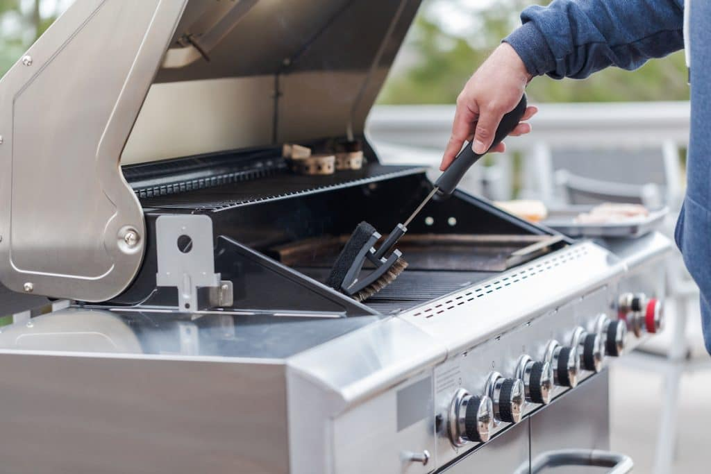 A zoomed in shot of someone brushing their grill.