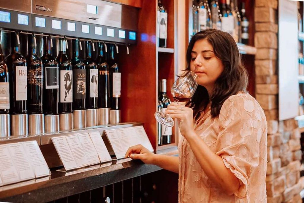 A woman smelling a glass of wine at Wine Room.